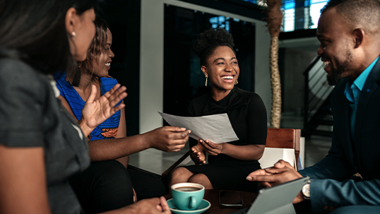 Black business colleagues discussing work while having coffee