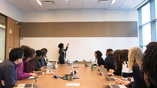 A female worker gives a conference presentation in a boardroom while her colleagues watch.