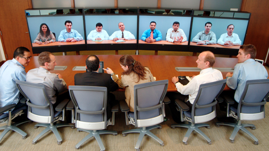 A group of HR workers have a virtual conference call with another group of workers in a boardroom.