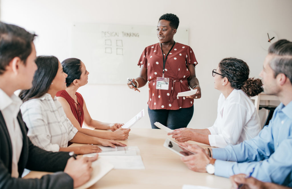 A woman is giving a presentation to her co-workers while holding notes in a conference room. He coworkers are gather around a table taking notes as they listen to her.