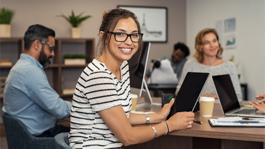 A female student intern smiles while participating in a boardroom meeting during her internship.
