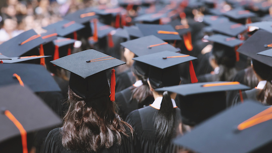 Backside view of university students wearing graduation hats during convocation ceremony.