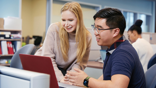 Male staff member helps female student with work on her computer in a university classroom.