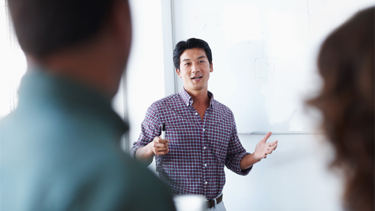A male graduate student gives a presentation to two attentive listeners.