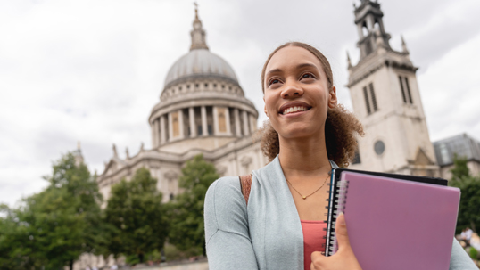 A female student holds her textbooks and smiles outside a historic building while on academic exchange.