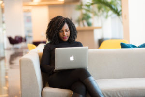 Black woman sits on sofa while using Apple laptop