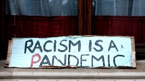 Cardboard sign with racism is a pandemic message written in marker