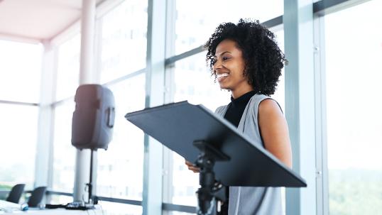 black woman speaking at podium
