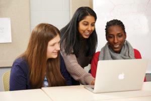 three female students using laptop