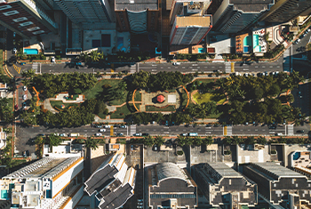 aerial view of boulevard with park and tall buildings