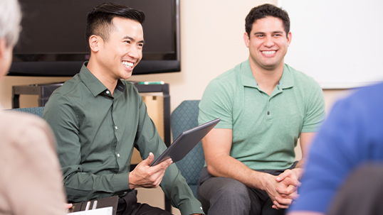 east asian and white male students smiling in group discussion