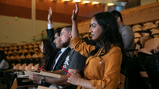 students raising their hands in lecture hall