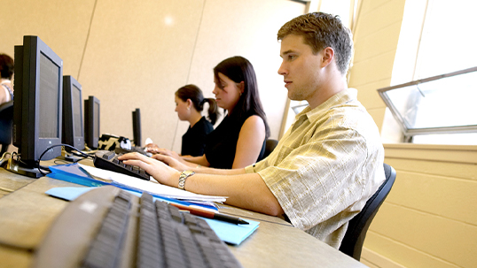 Students sitting at desks using computers