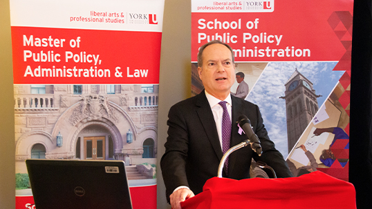 Man in formal attire stands at podium while giving presentation in front of York University public policy program branded posters