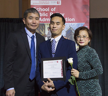 Justin Tan holding award while standing with his parents