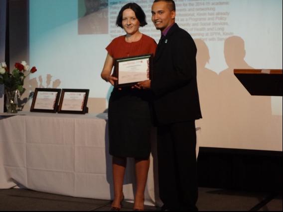 Kevin Baksh receiving award while standing next to Alena Kimakova