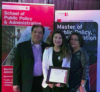 Melissa Calanza holding award while standing with parents