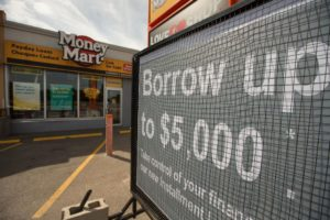 """photo of money mart and a sign with """"borrow up to $5,000, take control of your finances, our new installment"""""""
