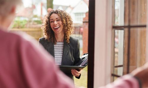 social worker greeting person in doorway