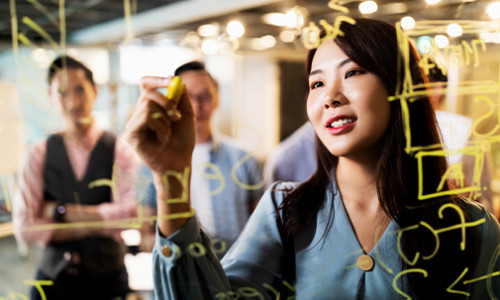 focus on young east asian woman using marker to write on transparent whiteboard