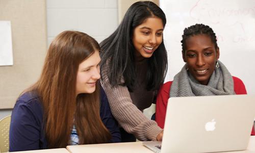 three female students around laptop