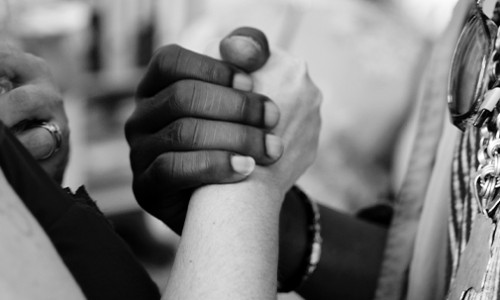 close up of white and black persons clasping hands