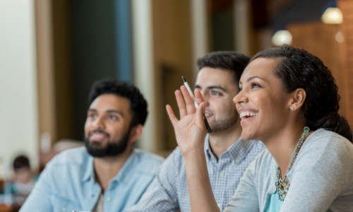 focus on cheerful female student raising her hand to answer question in seminar