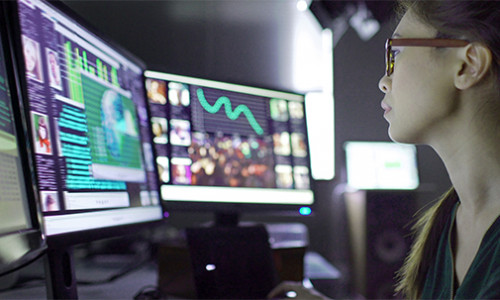 young female researcher studying crime trends on her computer screens