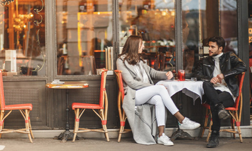 two fashionable young people chatting at cozy french cafe