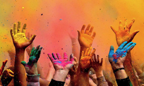 hands up in the air and festive colours in the background