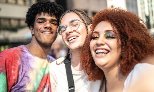 three cheerful individuals celebrating pride