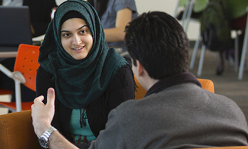 focus on woman in hijab interacting with her peer
