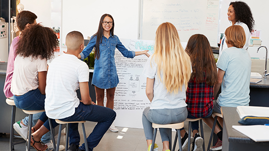 A student standing in front of other students giving a presentation