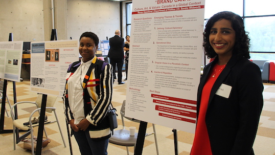 Two students smiling beside their DARE research projects