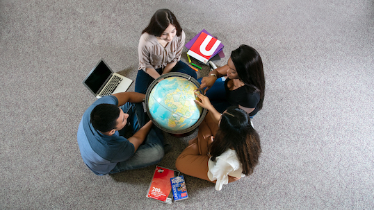 Students sitting around a globe
