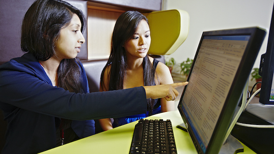 Two women sit at computer. One is a student getting help with Learning Skills Services