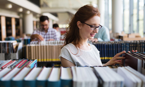 focus on woman browsing library books