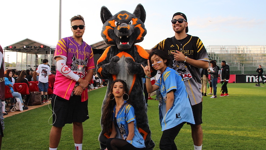 Members of McLaughlin's College at York University pose with a mascot wolf in orange and black