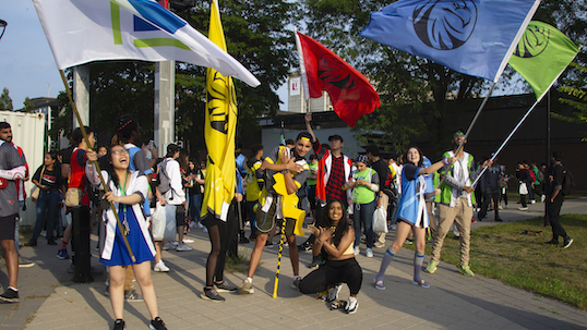 Students from LA&PS New College wave multicolored  flags and cheer at Keele campus