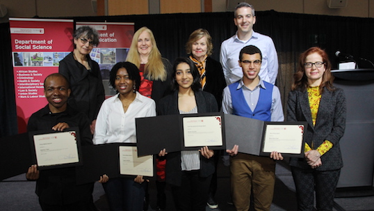 Students pose with their awards alongside professors