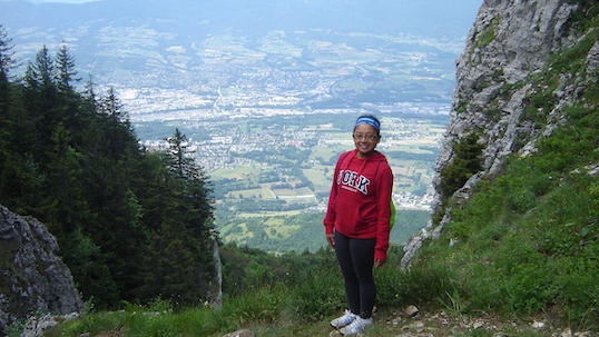York student in a red York sweater standing on a hillside smiling at the camera