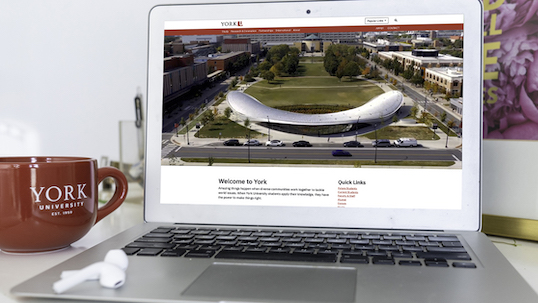 A closeup shot of a laptop on the Welcome to York homepage. A red York coffee mug is beside it and a pair of wireless headphones rest on the laptop