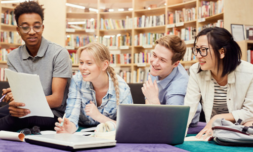 four diverse students in library