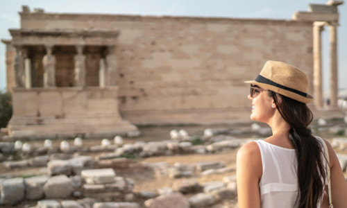 young female student exploring ancient greek ruins