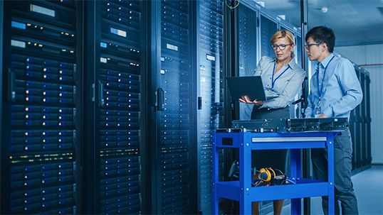 woman standing with male student in server room showing something on computer