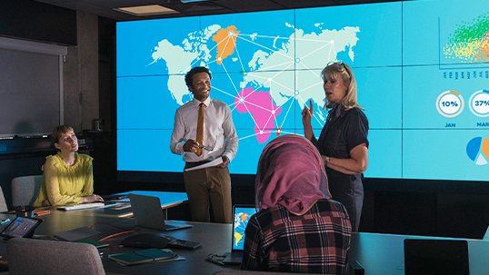 two people standing, two people sitting, discussing in front of map of the world on tv screens