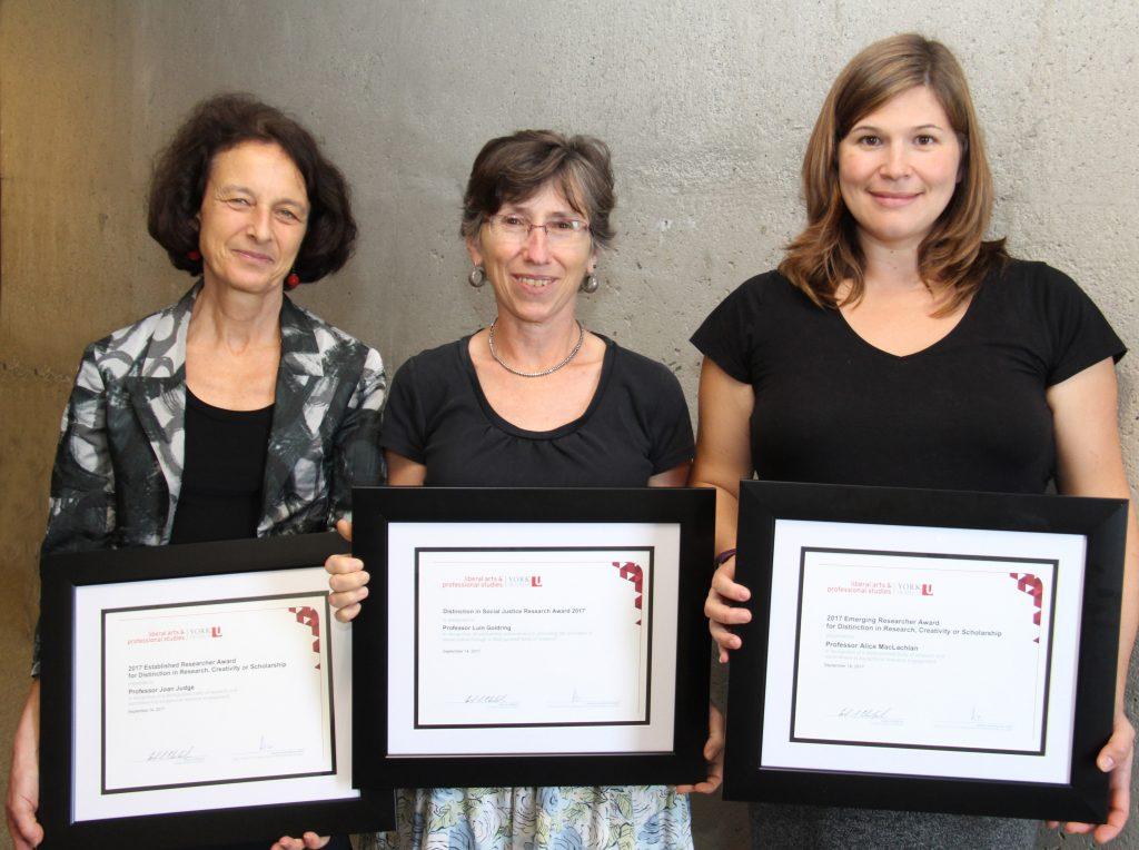 Three women pose for photo while holding teaching awards
