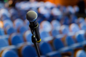 Microphone on stage in front of empty lecture hall