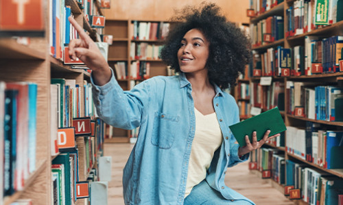 black girl sitting on floor of library looking at shelves