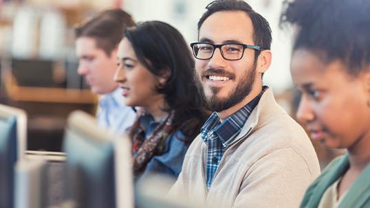 Hispanic man smiles while using laptop computer in college setting